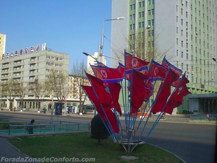 """Bandeiras da Coreia do Norte em uma esquina - de acordo com nosso guia, o vermelho representa o sangue dos revolucionários, o azul representa a esperança, o branco representa a mente clara do """"nosso"""" povo, e a estrela representa a história"""