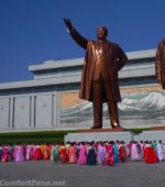 North Korean women bowing in traditional clothing to statues Kim il-Sung and Kim Jong-il Pyongyang