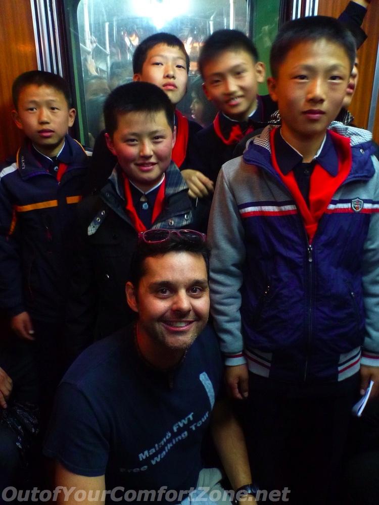 western foreigner with local North Korea schoolchildren Pyongyang in metro